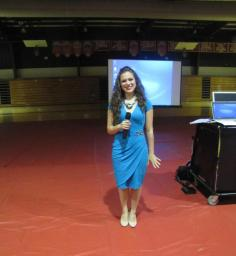 Victoria stands in a high school gymnasium with a microphone in hand.